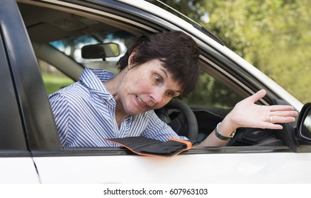 Annoyed woman sitting in her car discovers her wallet is empty.