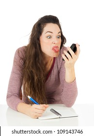 An annoyed woman is sticking her tongue out at her mobile phone. Isolated on white.
