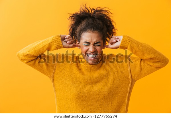 Annoyed young african woman wearing sweater standing isolated over yellow background, cover ears