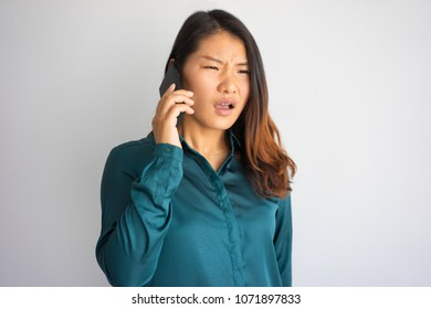 Annoyed young Asian woman in casual wear speaking on phone. Girl getting bad news or having unpleasant talk. Communication and bad news concept