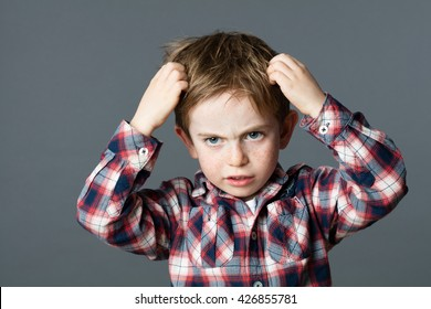 annoyed young boy with freckles scratching his hair for head lice or allergies, grey background studio