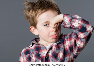 annoyed young child pinching his nose for sign of bad smell, sticking out his tongue for cheeky humor and mischievous childhood, grey background