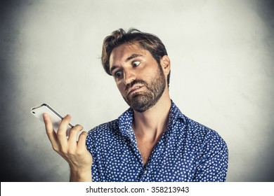 Annoyed young man at mobile phone