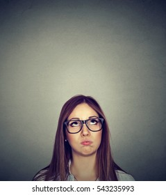 Annoyed young skeptical woman looking up isolated on gray wall background with copy space above head. Human emotions, feelings