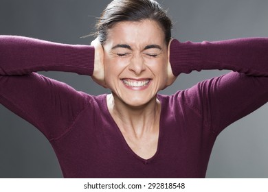 annoyed young woman covering closed ears, annoyed by loud noise, ignoring someone, not wanting to hear their side of story or having painful headache