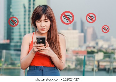 Annoyed young woman looking at smartphone having problem with no network coverage on screen and in city.