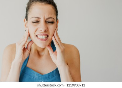 Annoyed young woman suffering from toothache and touching jaw. Irritated girl with closed eyes gritting teeth from pain. Hurt concept
