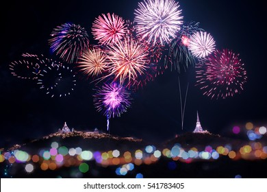 Annual fireworks festival displaying over temple on the mountain.  Firework sparkling in dark sky celebrating for religious temples on the top of the hills