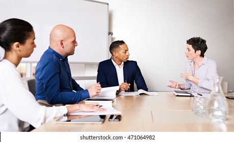Annual general meeting taking place in modern board room at conference table in new modern offices, with caucasian woman busy explaining the details of her motion to the other member of the board.