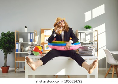 Annual leave and planning travel vacation concept. Funny office worker waiting for summer holidays. Happy barefoot employee in sun hat, sunglasses and swim ring sitting on desk and drinking cocktail