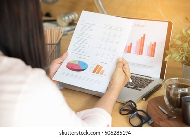 Annual report (cover,summary report,financial,paper,document,graph,news) review by Working and business woman or journalist.Brochure design with laptop on table.Business woman and planner concept.