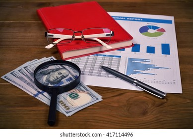 Annual report, glasses, dollars and pen on table