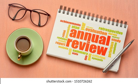 annual review word cloud on a digital  tablet with a cup of tea, business report, evaluation and summary concept