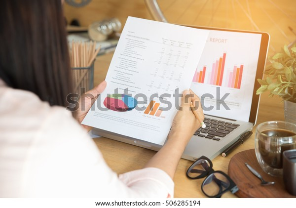 Annual summary report laptop and paper placed at office desk. Person back view of Asian woman work online and plan financial data with laptop, work from home. Business woman and planner concept.