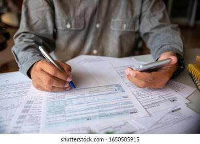 Budgetierung Konzept,Der Wirtschaftsprüfer berechnet die jährliche Steuer.Kalender 2020 und die Einkommenssteuerformulare für Personen, die Einkommen nach US-Recht auf Bürotheke haben.