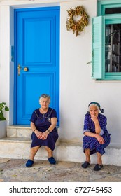 ANO KOUFONISI, GREECE - JUNE 14 2017: Elderly women sit outside house with blue door on Ano Koufonisi island in the Greek Cyclades.
