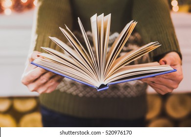 Anonymous adult woman dressed in green casual woolen sweater holding open blue book in hands with turning pages. Close up of female hands and book. Horizontal color photo