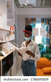 Anonymous African American shopper in casual wear and Afro hairstyle with sterile mask on face choosing book while standing in book mall during COVID 19 pandemic