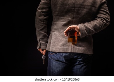 Anonymous alcoholic holding bottle of alcohol behind his back and car key. Don't Drink for Drive