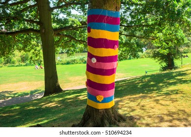 Anonymous art to give color to our grey cities. A tree in a park is dressed with knitted colorful wool. Knitting street art, called yarn bombing or yarn-storm. An open and joyful uncredited exhibition