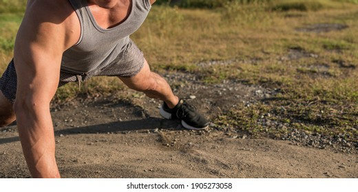 An anonymous athlete doing one arm pushups on the ground during a fair morning outdoors. Calisthenics and upper body strength and balance.