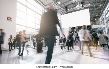 Anonymous blurred business people walking in a hall of a Exhibition
