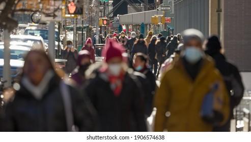 Anonyme unscharfe Menschenmenge, die mit Masken auf der Straße spaziert
