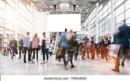 anonymous blurred people rushing at a trade fair