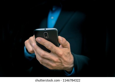 anonymous business men holding mobile smartphone in hand - dark black background