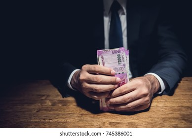 Anonymous businessman holding money, Indian Rupee currency, at the table in dark private room -  bribery, venality and corruption concepts
