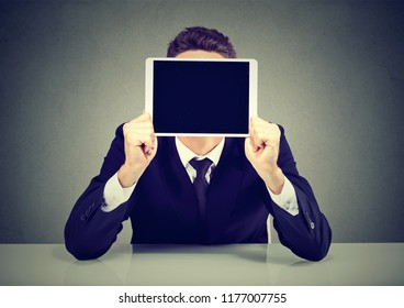 Anonymous businessman in suit holding tablet in front of face sitting on gray background
