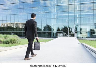 Anonymer Geschäftsmann oder Arbeiter in schwarzem Anzug mit Lederhandtasche oder Laptop-Gehäuse in der Hand geht zur Arbeit auf der Straße zum Eingang eines gläsernen Bürogebäudes.