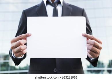 Anonymous businessman or worker in black suit with tie and shirt holds a white sheet of paper in hands.