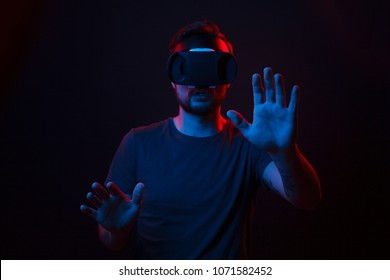 Anonymous casual man wearing VR goggles and touching air in front exploring new feelings in dark neon lights.