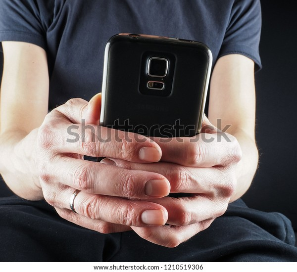 Anonymous caucasian person holding a phone in folded hands at closeup, wearing black clothes on black