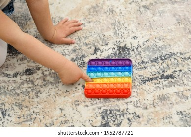 Anonymous child playing with the colorful pop It fidget. Close up kid hands playing with the colorful poppit toy in home.