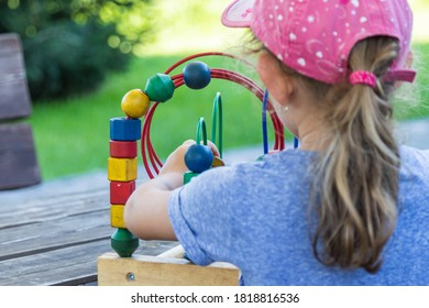 anonymous child playing with wooden puzzle game