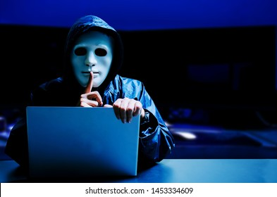 Anonymous computer hacker in white mask and hoodie. Obscured dark face making silence gesture in Underground Secret Location Surrounded by Displays and Cables, darknet and cyber security concept.
