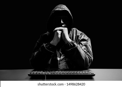 Anonymous computer hacker in white mask and hoodie. Obscured dark face with keyboard computer in the dark. Data thief, internet attack, darknet and cyber security concept.