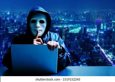 Anonymer Computer-Hacker in weißer Maske und Kapuze. Verdecktes dunkles Gesicht mit Stille Geste auf modernen Stadthintergrund, Data Dieb, Internet-Angriff, Dunkelnetz und Cyber-Sicherheit Konzept.