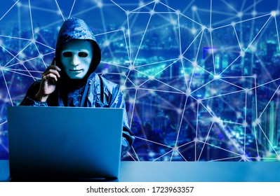 Anonymous computer hacker in white mask and hoodie. Obscured dark face using laptop computer for cyber attack and calling on cellphone on modern city background, Data thief, internet attack, darknet.
