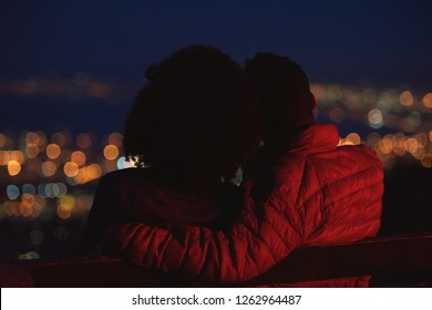 Anonymous couple on a romantic date, looking at city lights young romance