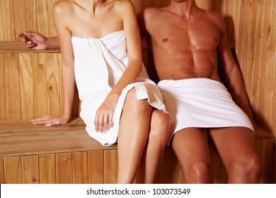 Anonymous couple sitting next to each other in sauna