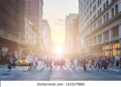 Anonymous crowd of people cross the intersection on a busy New York City street in Manhattan with sunlight background