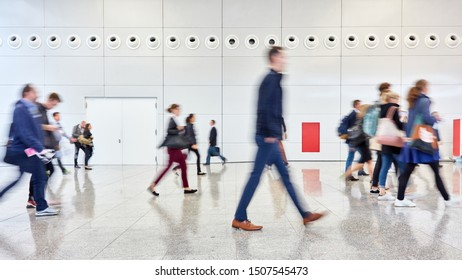 Anonymous crowd of people goes through hall of a trade fair or airport