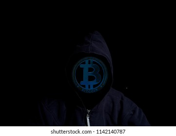 Anonymous Crypto Hacker in hood with bitcoin isolated on black background