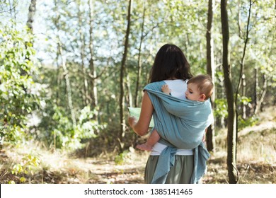 Anonymous European mother babywearing one year old on a hike in the forest.