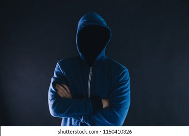 Anonymous and faceless man under hoodie with arms crossed isolated over dark background - incognito and mysterious criminal on internet activities concept