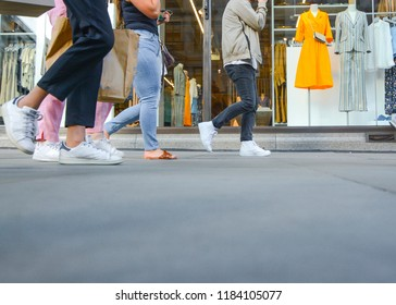 Anonymous feet and legs of shoppers walking past a shop window displaying fashionable clothes