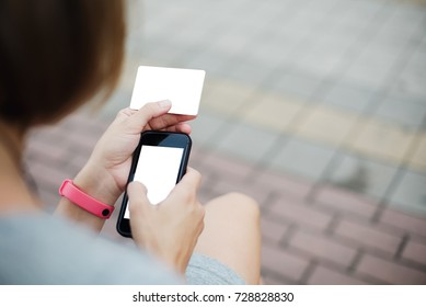 Anonymous girl browsing smartphone while holding card and sitting outside doing online purchases.